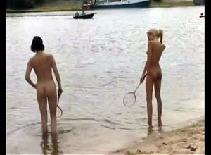 Slim bare youngsters toying badminton..